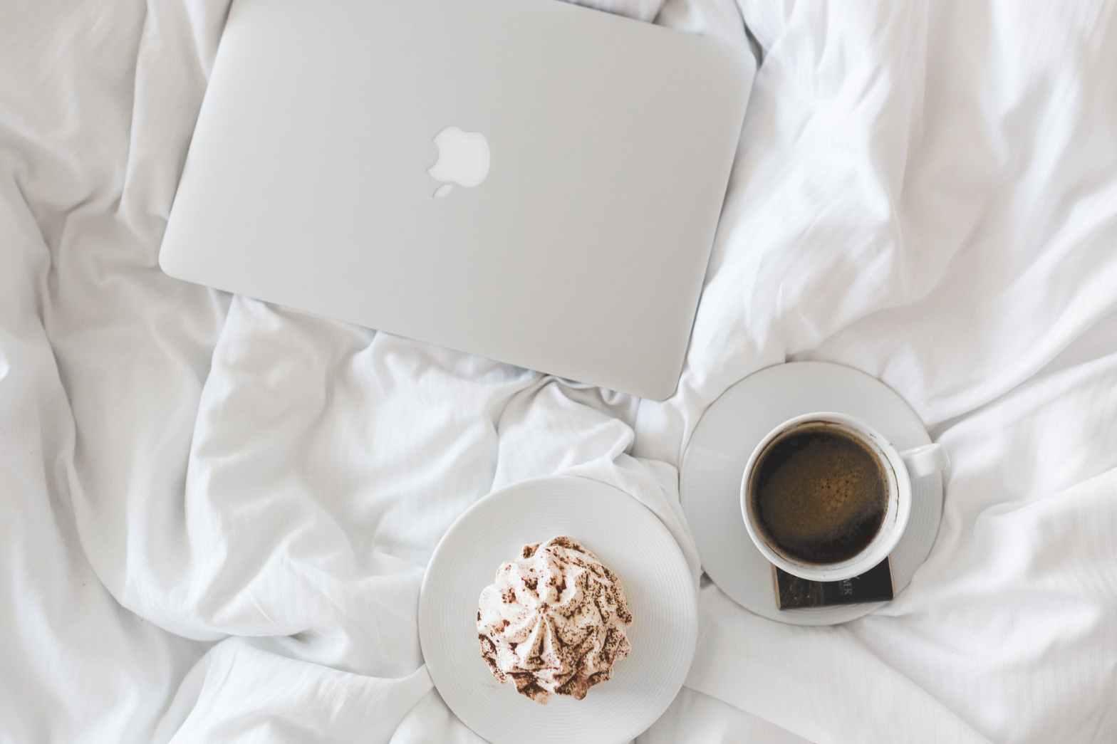 vue en contre-plongée sur un lit à la couette blanche comportant une boisson chaude et une pâtisserie