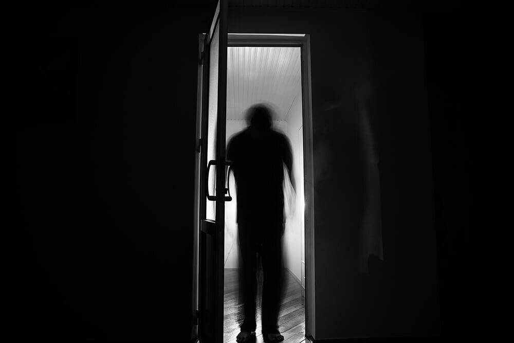 silhouette noire diforme à travers une porte