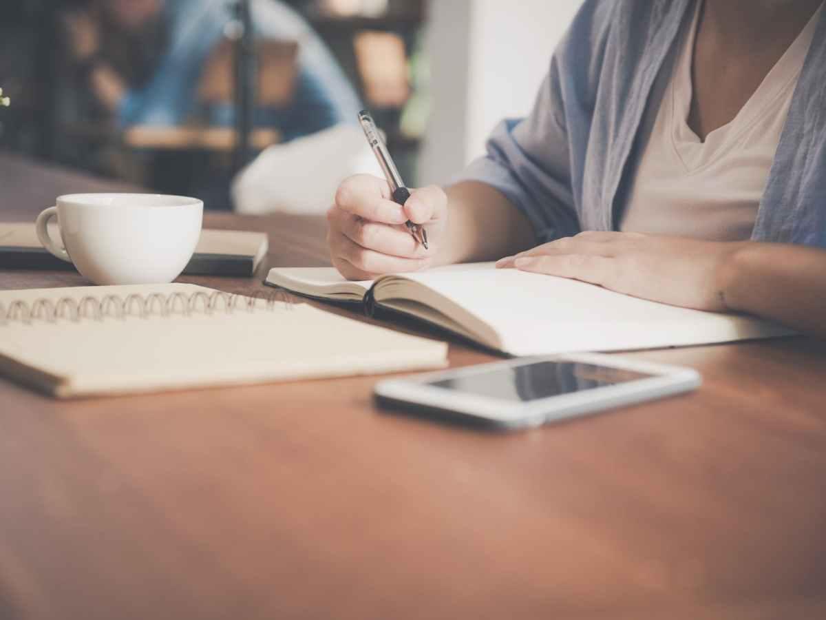 vue poitrine d'une personne qui écrit dans un carnet accompagnée de son téléphone et d'une boisson chaude