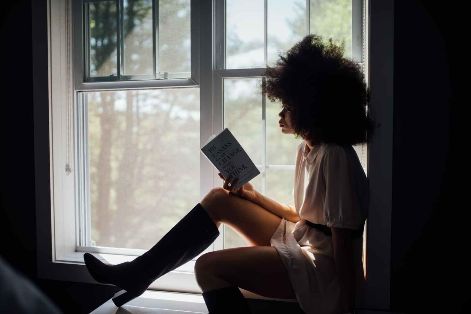 Silhouette d'une femme assise à la fenêtre lisant un livre