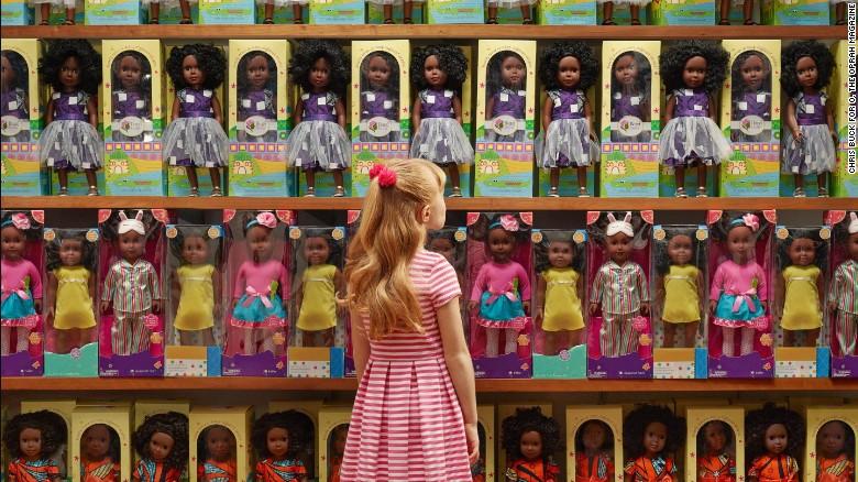 """""""Let's talk about race"""" - CHRIS BUCK FOR O MAGAZINE  Petite fille blanche se tenant devant un rayon constitué uniquement de poupées à la peau noire."""